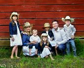 picture of denim wear  - Family of seven pose besides red wooden barn. Females are wearing denim jackets and cowboy hats. Males are wearing jeans and white shirts.
