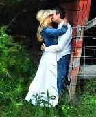 stock photo of she-male  - Young couple embrace behind the barn. She is wearing a white dress with cowboy hat. He is wearing jeans and a white shirtl