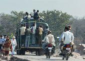 Orchha, India - February 2011 - Overloaded Public Transport Bus Carrying People On top and sides.