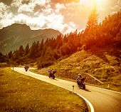 Group of motorcyclists riding on curves mountainous road, race of motorbike in Alps, beautiful pine forest, red sunset light, extreme sport concept