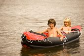 stock photo of inflatable slide  - two boys in a rubber boat at the lake - JPG