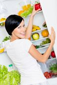 Woman takes bell pepper from the opened refrigerator full of vegetables and fruit. Concept of healthy and dieting food