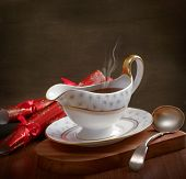 Rich gravy served in gravy boat with ladle and Christmas crackers