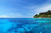 Blue Sea With Coral Reef And Fluffy Clouds From Tachai Island In Thailand