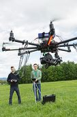Young male technicians flying UAV spy drone in park