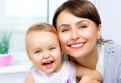 Mother and Baby kissing and hugging at Home. Happy Smiling Family Portrait. Mom and her Child Portrait
