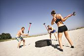 stock photo of striking  - Three strong athletes doing hammer strike on a truck tire during exercise outside on beach - JPG