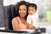 beautiful african american businesswoman holding her baby in office