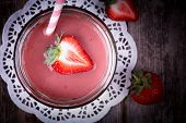 Strawberry smoothie in glass jar, over old wood table. Vintage effect with intentional vignette