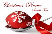 Christmas dinner concept.  Stainless steel serving spoon with Christmas ornament and satin ribbon on