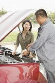 Woman and Mechanic Working on Car