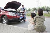 Mother and Daughter Watch as Father and Son Try to Fix the Car