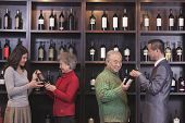 Four People Examining Wine Bottles at a Wine Store