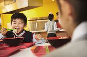 stock photo of noodles  - School boy eats noodles in school cafeteria - JPG