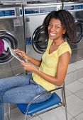 Portrait of happy young woman with digital tablet sitting in laundry