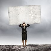 Image of businesswoman holding stone on her shoulders