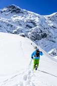 Skiing in fresh powder snow - Man with skis climbs to the top