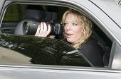 picture of private investigator  - female private investigator spy or secret agent taking photographs from car - JPG
