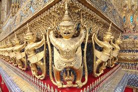 stock photo of mahabharata  - The statues of Garuda battling naga serpent on the wall of temple in Thailand - JPG