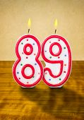 Burning birthday candles number 89 on a wooden background