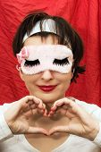 Attractive Woman In Sleep Mask Making Heart Shape With Her Hands