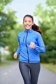 Happy woman runner healthy lifestyle concept with girl jogging smiling training outside in park for
