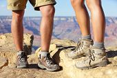 Hiking shoes on hikers in Grand Canyon. Man and woman hiker hike boots in closeup with breathtaking view of Grand Canyon in the background. Male and female feet.