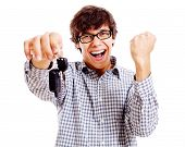 Screaming young man with car keys and raised fist isolated on white background