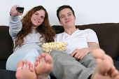 Young Couple Watching Tv And Eating Popcorn