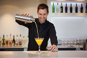 foto of bartender  - Smiling bartender pouring yellow cocktail into glass at the bar - JPG