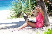 Blond Girl With A Laptop On Tropical Beach