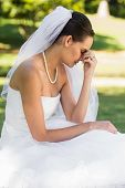 Side view of a beautiful worried bride sitting at the park