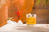 Whisky liqueur glass with ice cubes on the sandy beach