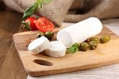 Tasty bushe cheese with tomatoes, olives and basil, on cutting board