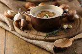 Composition with mushroom soup in pot, fresh and dried mushrooms, on wooden table, on sackcloth back