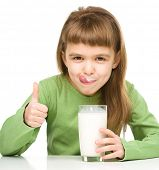 Cute little girl showing milk moustache and thumb up sign, isolated over white