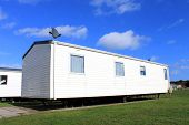 Side view of trailer on caravan park with blue sky and cloudscape background.