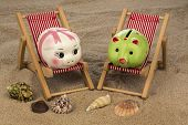 deck chair with piggy bank on the sandy beach. symbolic photo for travel costs, holidays, vacations. save on holiday