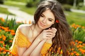 Enjoyment. Blowing Long Hair. Free Happy Woman Enjoying Nature. Beauty Girl Over Marigold Flowers Fi
