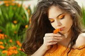 stock photo of marigold  - Outdoors portrait of Beautiful Teen girl smelling flower over marigold flowers field - JPG