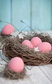 pink easter eggs on the table in nest