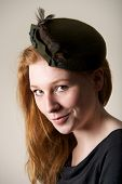 Redhead smiling cheekily in green feathered hat