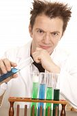 stock photo of mad scientist  - A mad scientist is ready to pour chemicals together using test tubes - JPG