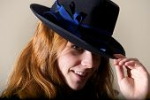 Redhead smiling in black hat touching brim