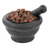 Red sage root chinese herbal medicine in a black stone mortar with pestle over white background. Dan