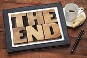 the end - text in vintage letterpress wood type on a digital tablet with a cup of coffee