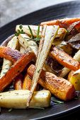 Roasted root vegetables on a black serving platter.  Carrots, parsnips, turnips, red onions, and her