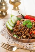 Spicy fried noodles. Indonesian and Malaysian cuisine, mi goreng or mee goreng mamak with wooden din