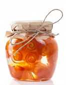 Glass jar with citrus zest preserves isolated on white background