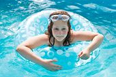 Girl On Swimming Circle In Blue Open-air Pool